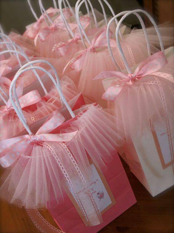 Decoração de chá de bebê com cupcake com sacolinhas rosas como lembrancinhas