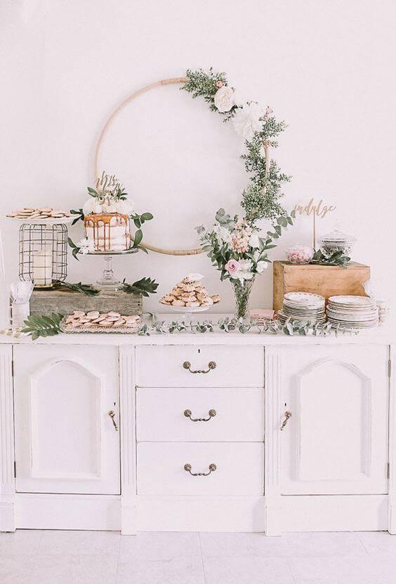 Decoração de chá de bebê com mesa de doces com folhas e flores