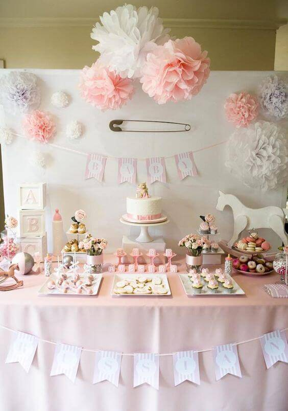 Decoração de chá de bebê com mesa de doces com pompons