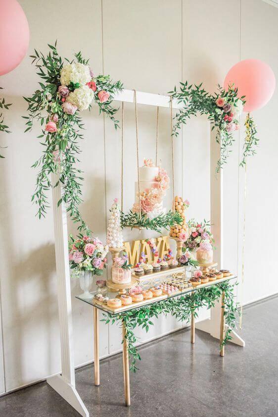 Decoração de chá de bebê com mesa de doces com flores