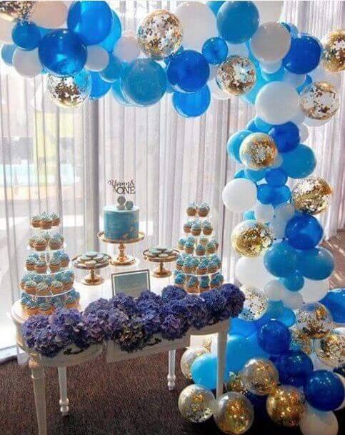 decoracao de festa com bexigas e mesa de cupcakes