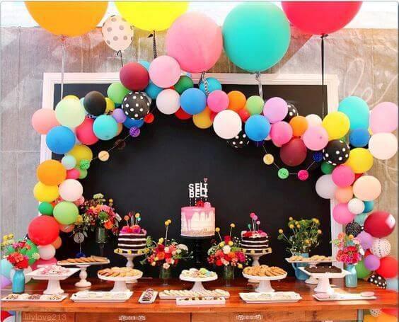 decoracao de festa mesa de bolo com bexigas coloridas