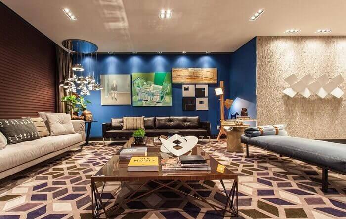 Mesa de centro retangular e parede azul complementa a decoração da sala de estar