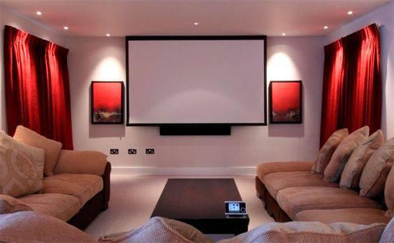 cinema em casa com cortinas vermelhas e quadros