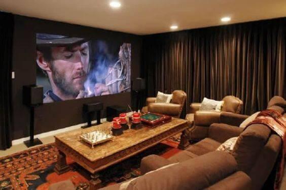 cinema em casa com mesa de centro e poltronas marrons