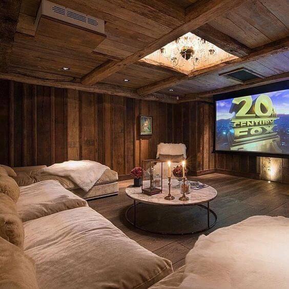 cinema em casa com revestimento de madeira e lustre embutido