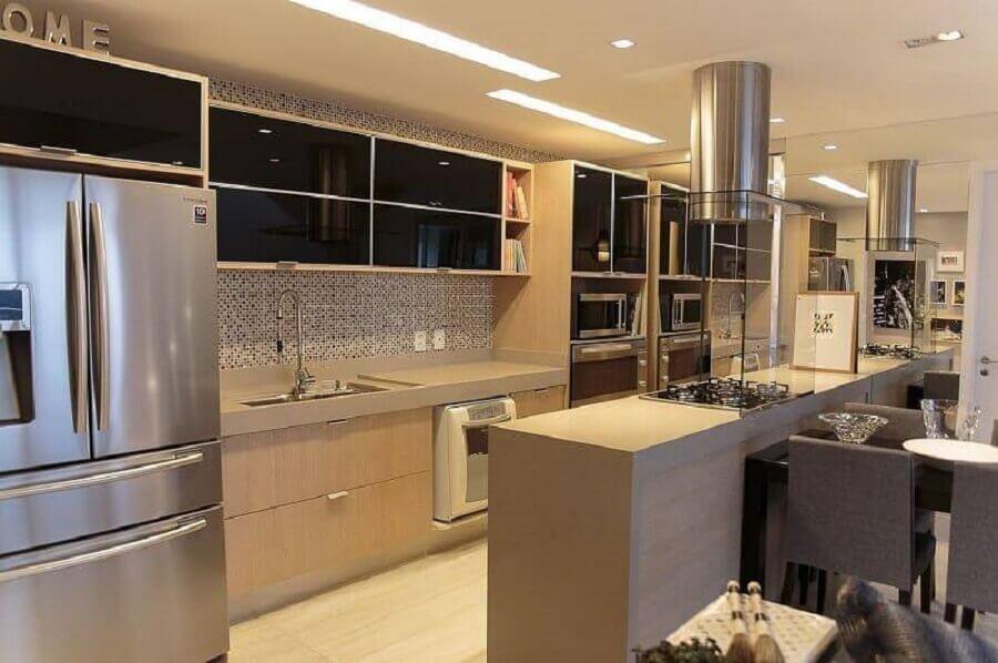 cozinha de apartamento decorada com bancada com cooktop e parede espelhada Foto Danyela Correa