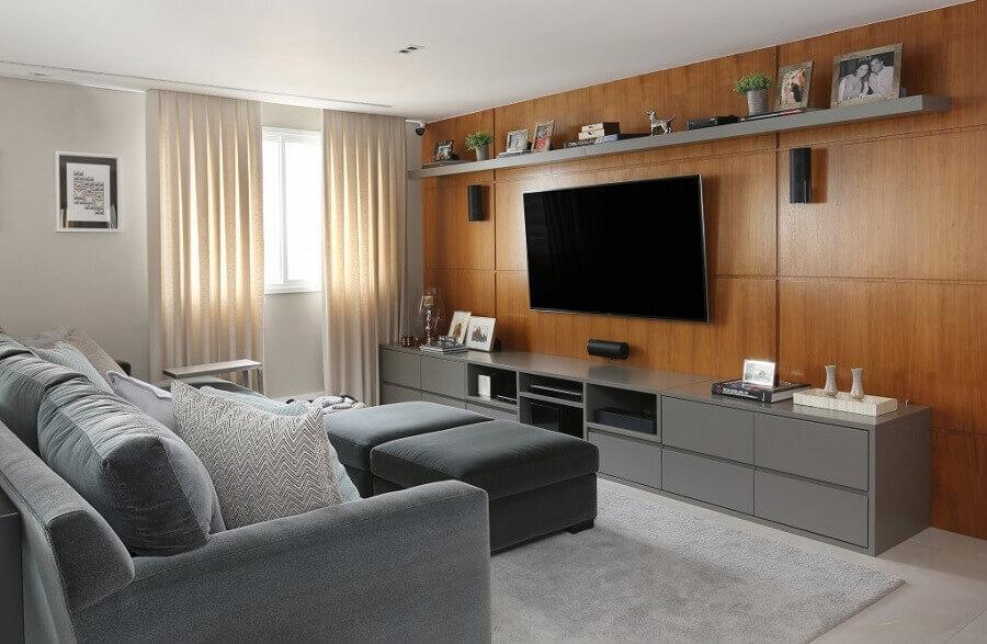 sala de apartamento decorado com painel de madeira e rack cinza Foto Karen Pisacane