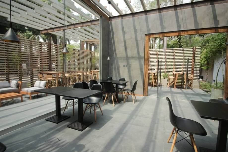 Área externa com teto de vidro e piso de cimento queimado Projeto de Casa Cor Paraguai