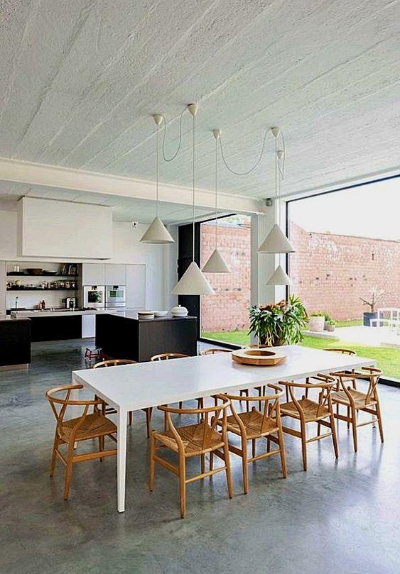 Casa com piso de cimento queimado e mesa de jantar branca