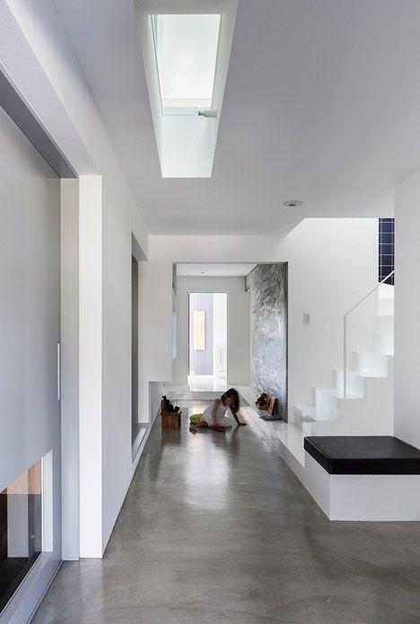 Casa com piso de cimento queimado e parede branca