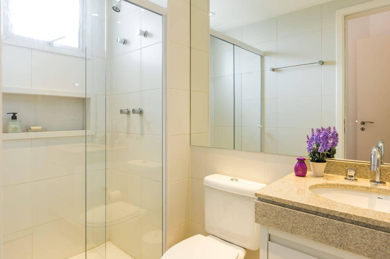 Decoração de banheiro clara com espelho grande, gabinete e nicho Projeto de By Arquitetura