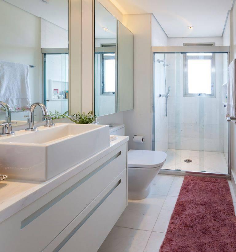 Decoração de banheiro clara com gabinete com gavetas e muitos espelhos Projeto de Luciana Tomas