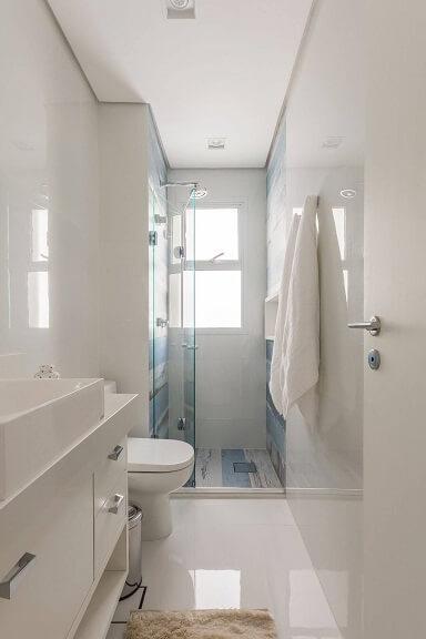 Decoração de banheiro clara com toque de cor no box que conta com nicho e porta de vidro sanfonado Projeto de Idealizzare Arquitetura