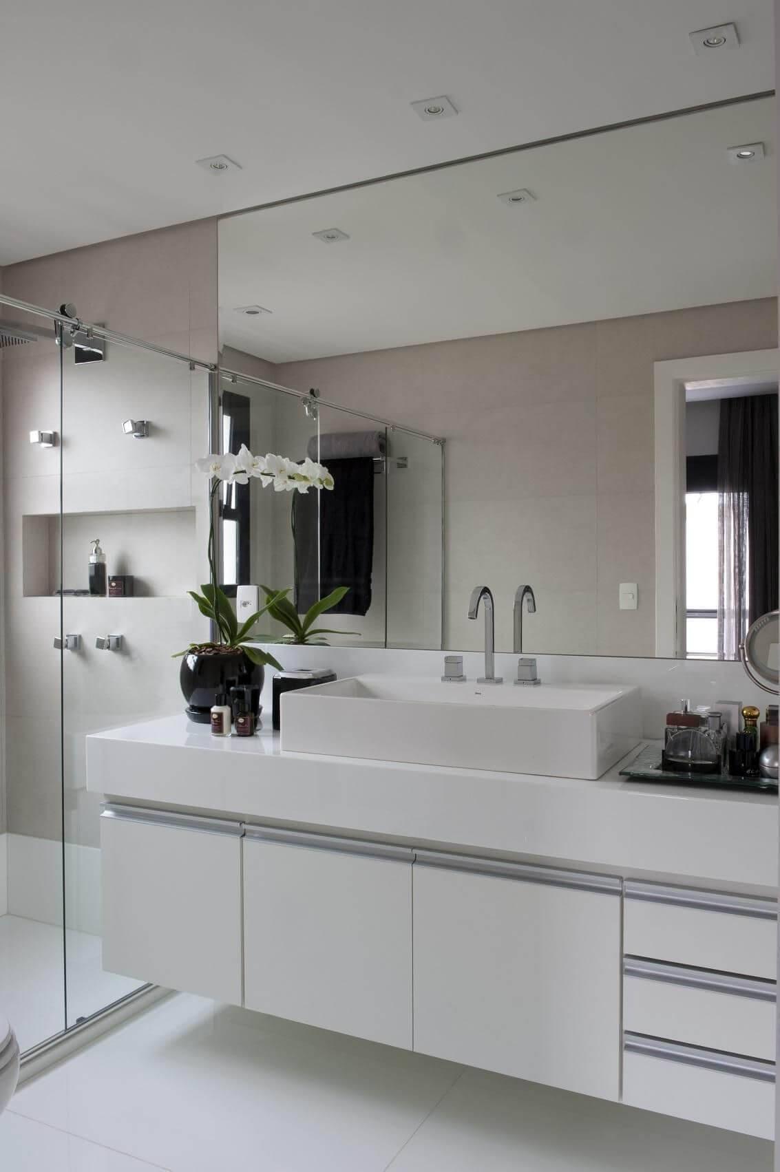 Decoração de banheiro com espelho amplo, gabinete com portas e gavetas e nicho Projeto de Jamile