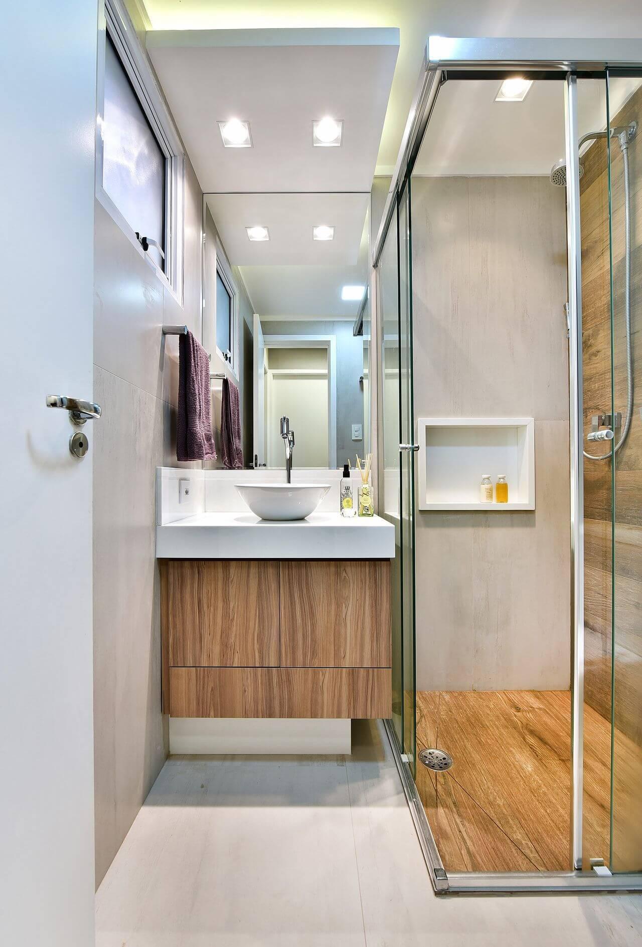 Decoração de banheiro com gabinete e chão do box de madeira. Projeto Tetriz Arquitetura