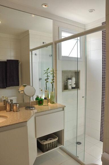Decoração de banheiro com gabinete e nicho abaixo da janela dentro do box