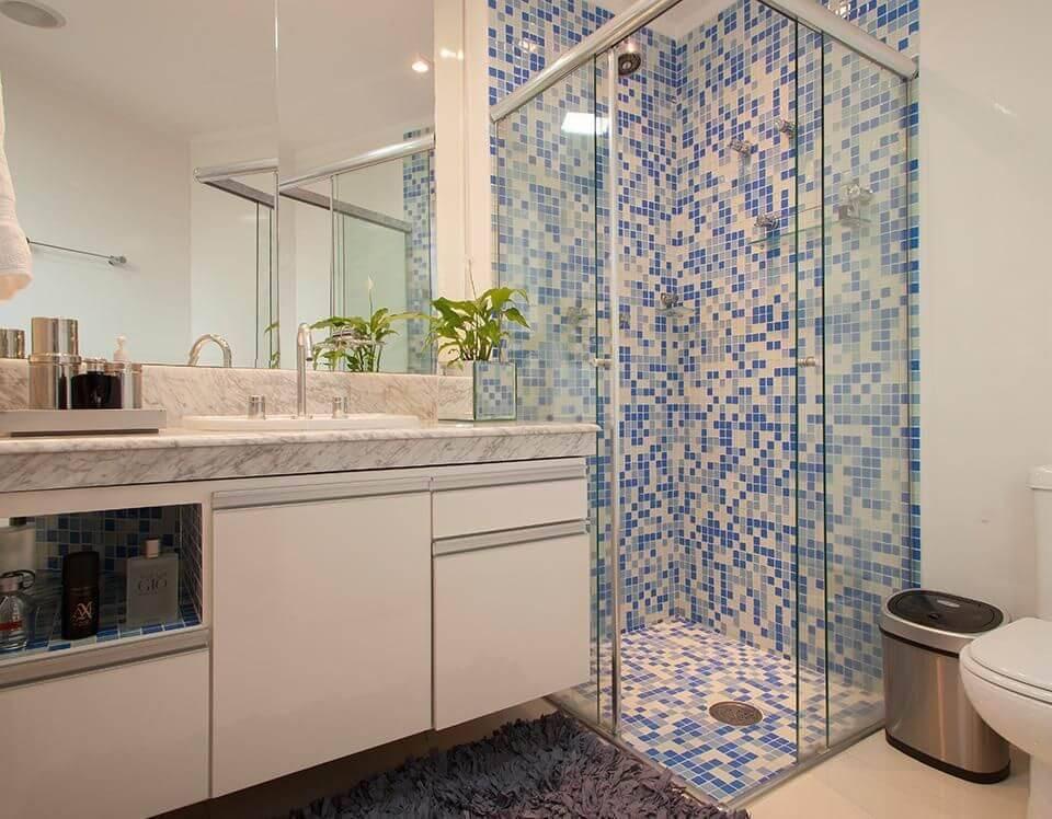 Decoração de banheiro com gabinete, espelho amplo e prateleiras de vidro dentro do box Projeto de Sandra Sanches