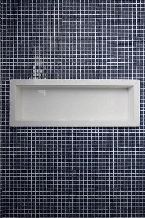 Decoração de banheiro com nicho de pedra embutido na parede de pastilhas Projeto de Lima Orsolini Arquitetura e Interiores
