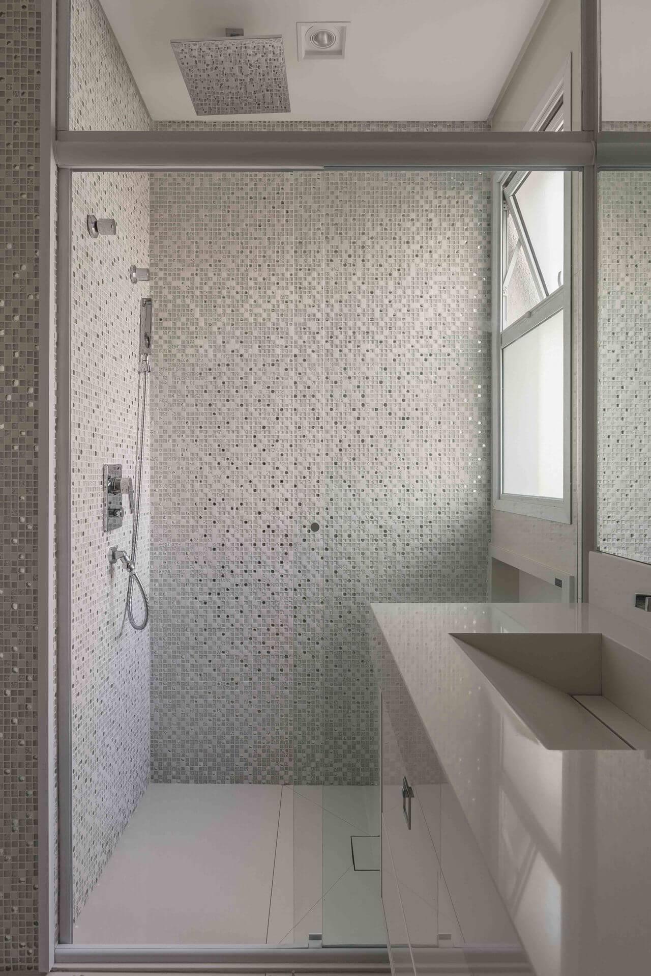 Decoração de banheiro com pastilhas, gabinete e espelho grande. Projeto de Idealizzare Arq