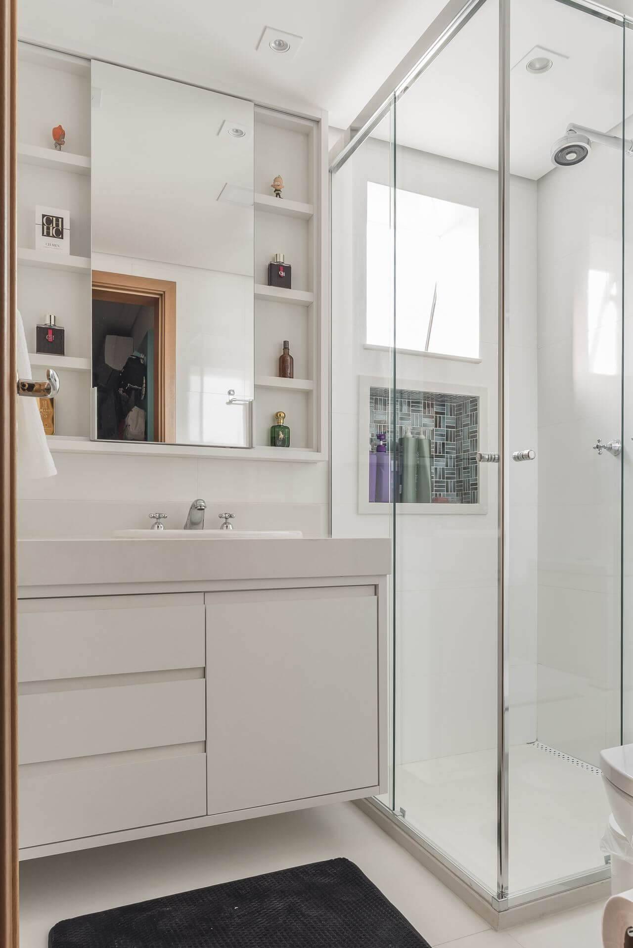 Decoração de banheiro com vários nichos aos lados do espelho, um dentro do box e gabinete Projeto de Sandra Pompe