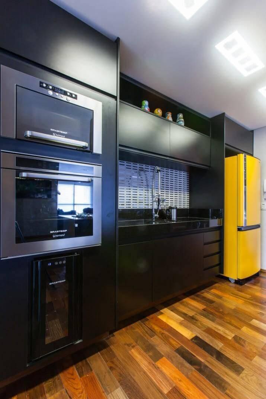 Decoração de cozinha planejada com armários pretos e envelopamento de geladeira na cor amarela Projeto MC3 Arquitetura
