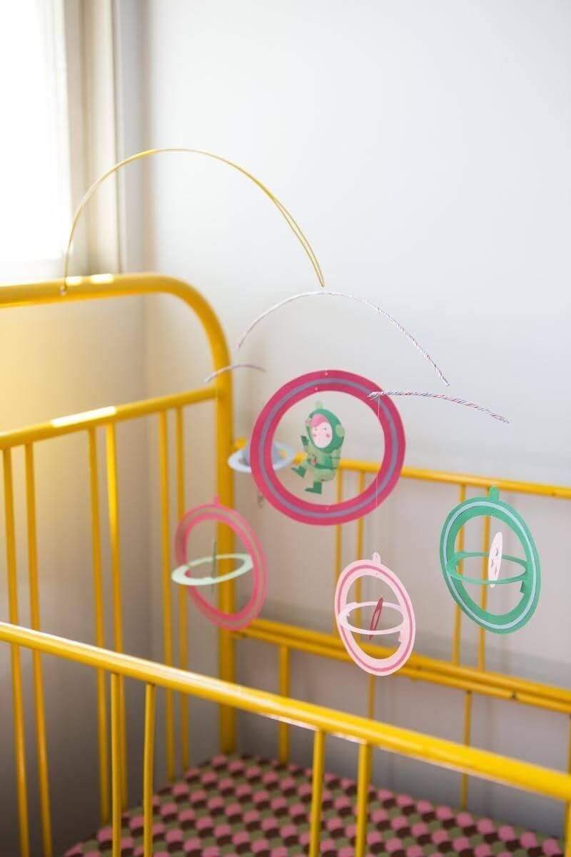 Decoração de quarto de bebê com berço amarelo e móbile colorido Projeto de Buji