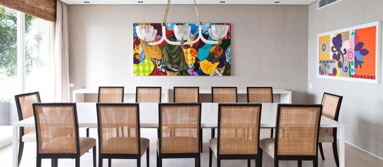 Decoração simples em sala de jantar com mesas brancas e quadros coloridos Projeto de Olegario de Sá