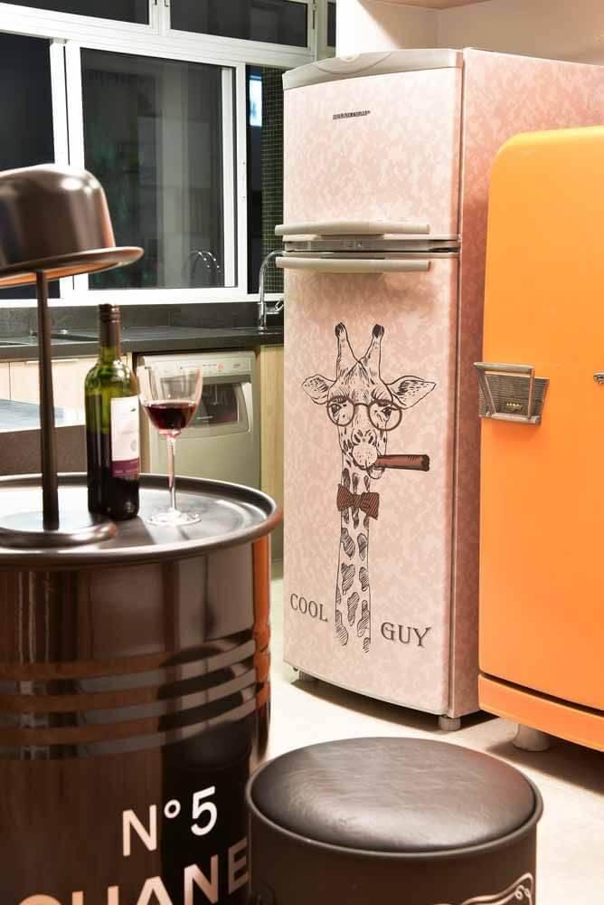 Detalhe de decoração de cozinha compacta com envelopamento de geladeira com estampa de girafa Projeto de Ana Yoshida