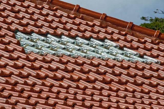 Dois tipos de telhas sendo usados em um mesmo telhado, de vidro e de cerâmica