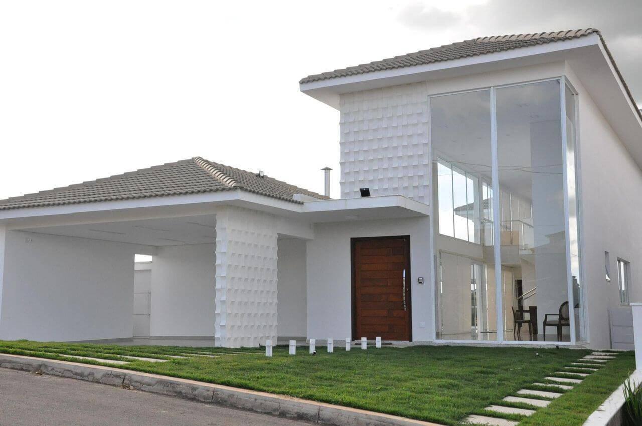 Fachada com a escolha por tipos de telhas acinzentadas combinando com o branco. Projeto de Cláudia Breias