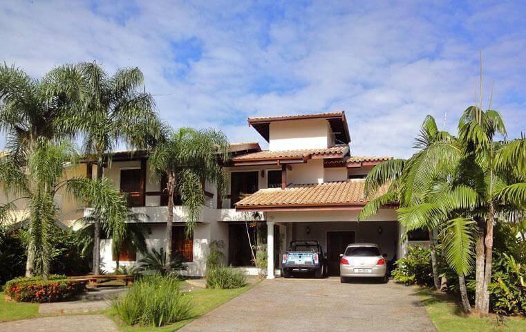 Fachada de casa com garagem ampla e tipos de telhas de cerâmica. Projeto de Danyela Correa