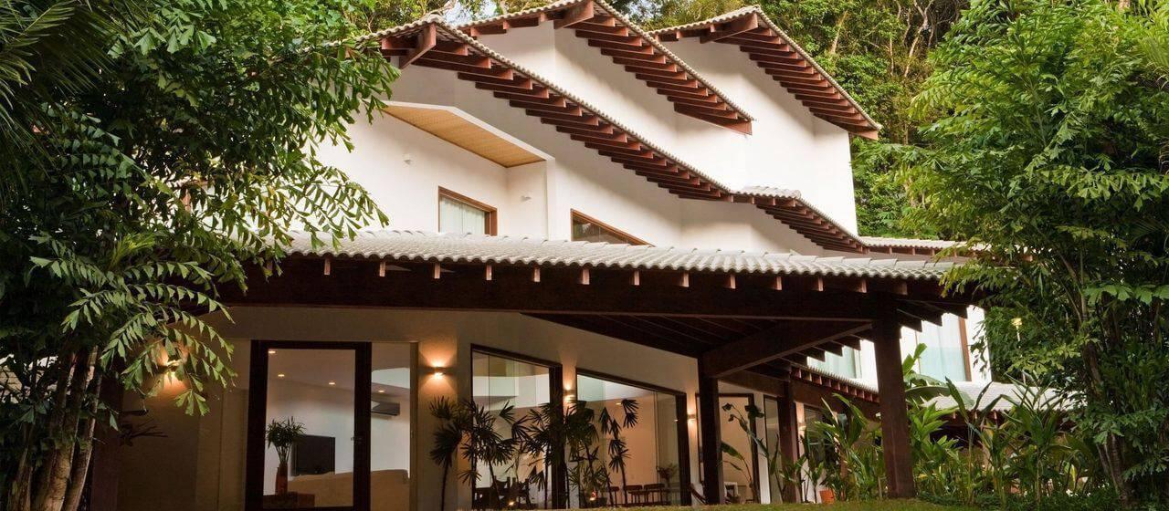 Fachada de casa com teto colonial e tipos de telhas acinzentadas. Projeto de Olegário de Sá