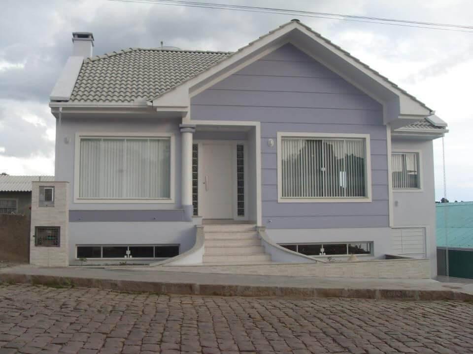 Fachada de casa estilo colonial em tons claros e tipos de telhas acinzentadas. Projeto de Denise Brighenti