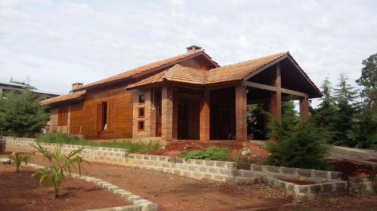 Fachada de residência rústica com tipos de telhas de cerâmica. Projeto de Anelise Morgan