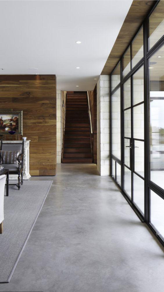 Sala com piso de cimento queimado e decoração madeira