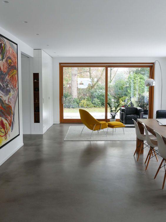Sala com piso de cimento queimado e poltrona mostarda
