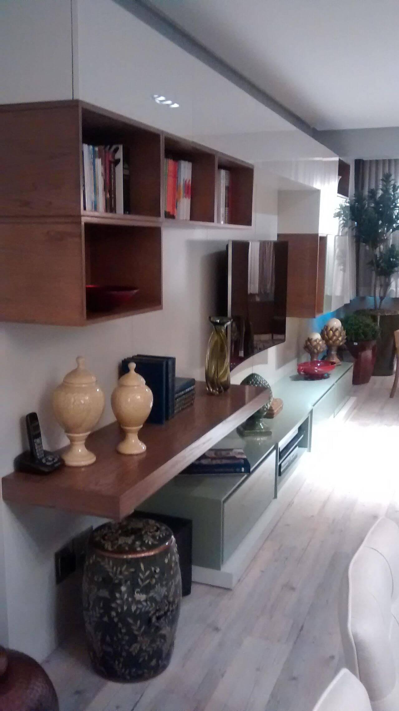 Sala de estar com nichos e prateleira de artesanato em madeira Projeto de Patricia Medeiros
