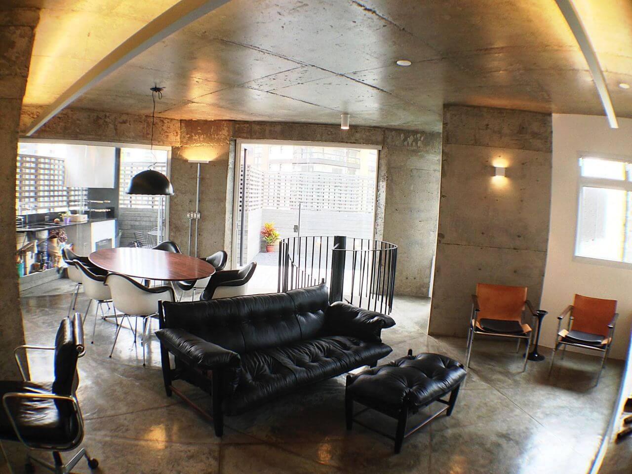 Sala de estar com piso de cimento queimado, paredes e teto com mesmo acabamento Projeto Odvo Arquitetura