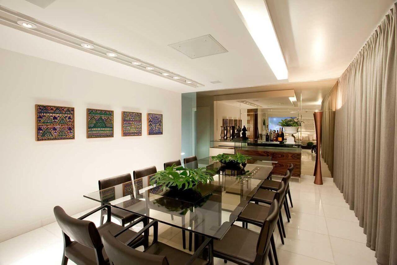 Sala de jantar ampla com uso de espelho na parede e mesa grande de vidro Projeto de LF Rezenda