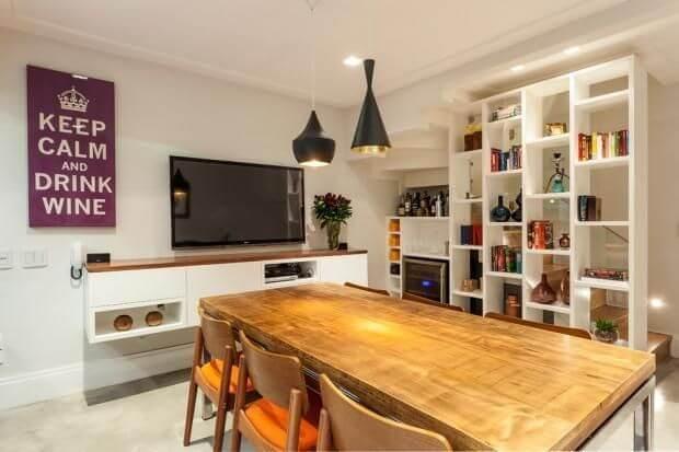 Sala de jantar com TV e estante com objetos de decoração Projeto de Arq In Arquitetura