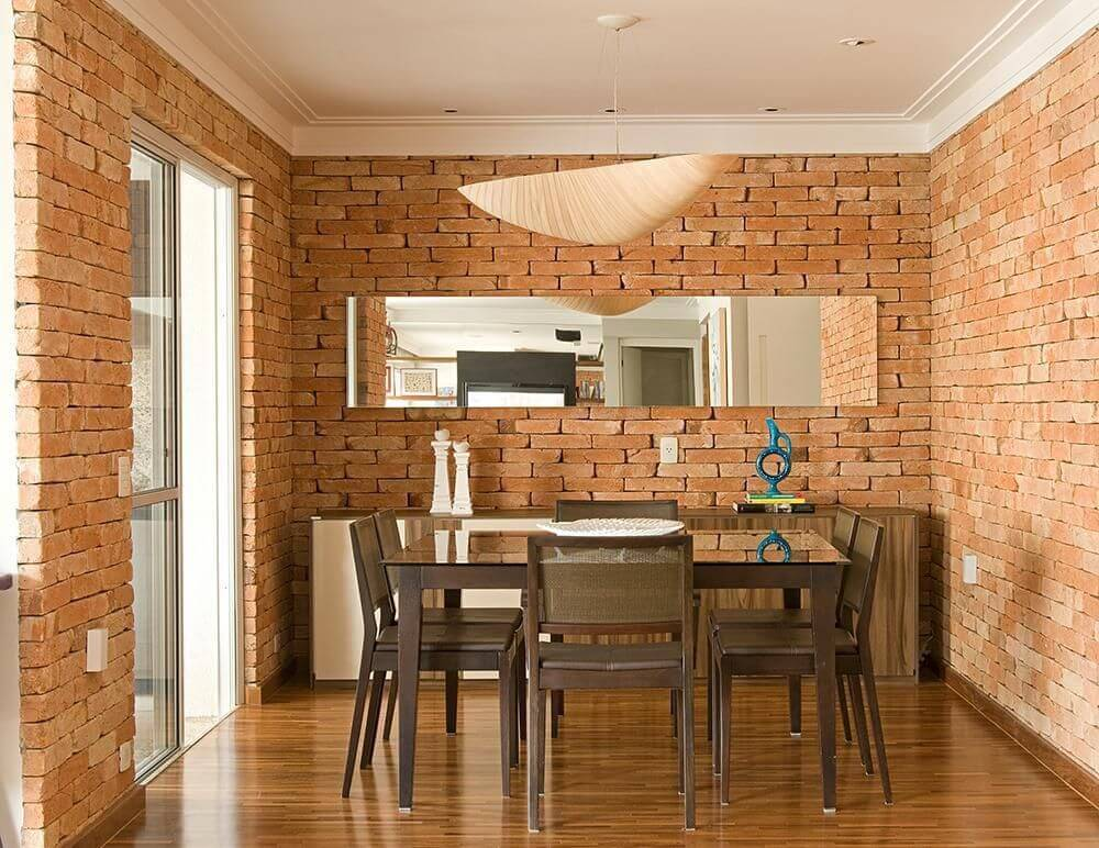 Sala de jantar com buffet e paredes de tijolos aparentes Projeto de Díptico Design de Interiores
