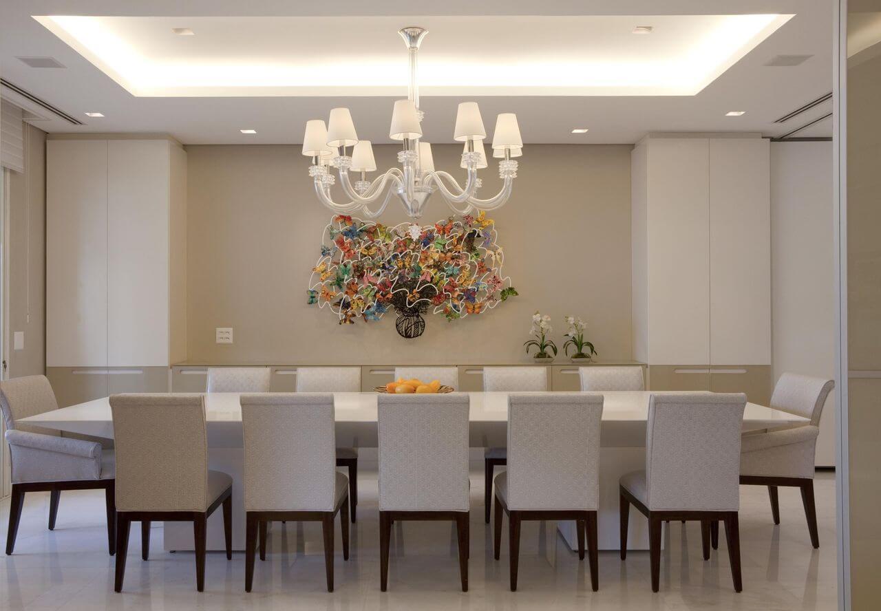 Sala de jantar com decoração clara e destaque para obra de arte colorida na parede Projeto de Marcelo Rosset