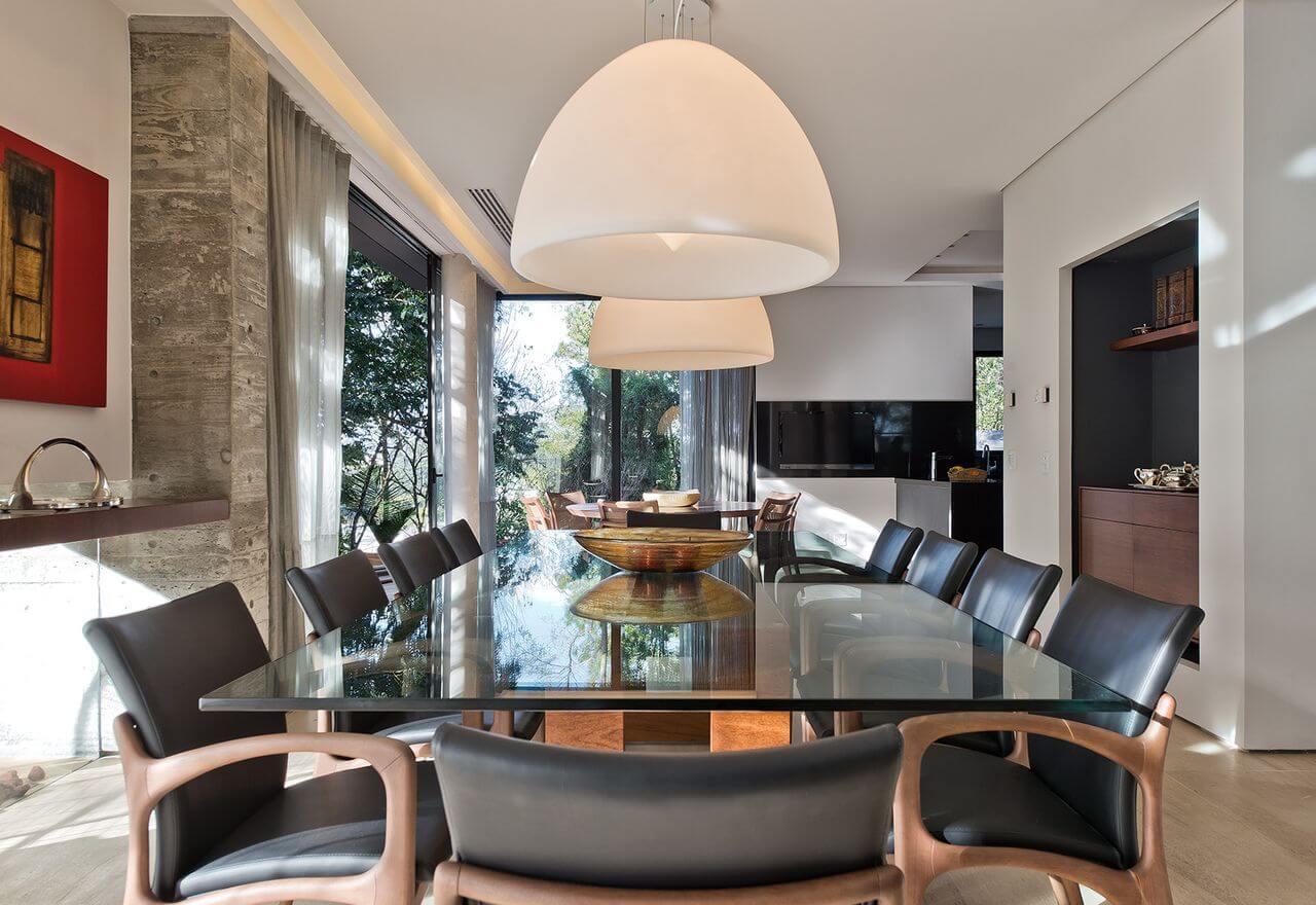 Sala de jantar com mesa de vidro e de madeira Projeto de Leonardo Muller]