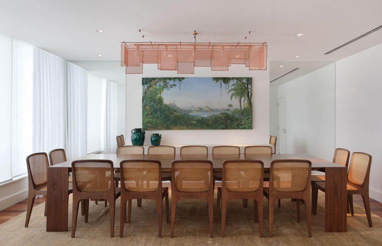 Sala de jantar com mesa grande de madeira e várias cadeiras Projeto de Paola Ribeiro