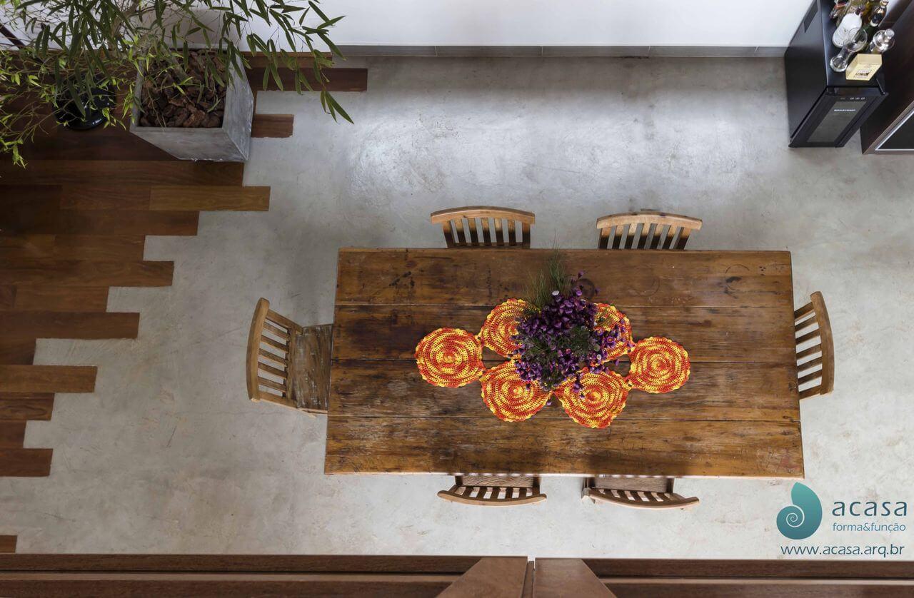 Sala de jantar com piso de cimento queimado encontrando com piso de madeira Projeto de A Casa