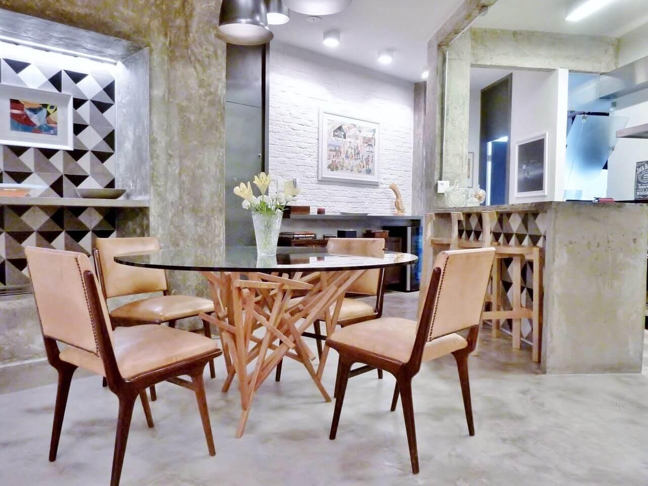 Sala de jantar com piso de cimento queimado, paredes e balcão com o mesmo acabamento Projeto de Adriana Fornazari