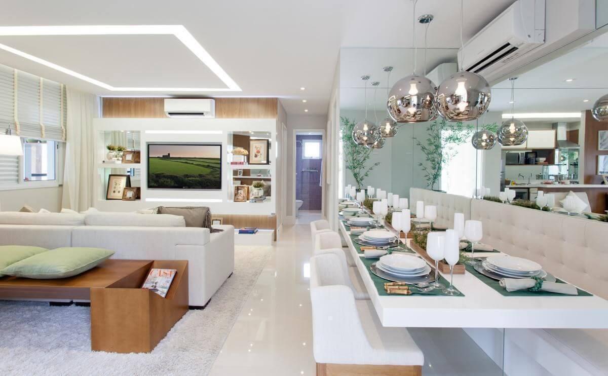 Sala de jantar com sofá e mesa encostada na parede integrada à sala de TV Projeto de Sesso e Dalanezi