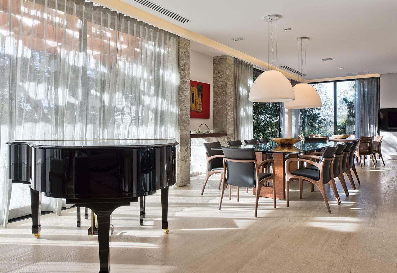 Sala de jantar grande com duas mesas de jantar e um piano Projeto de Leonardo Muller