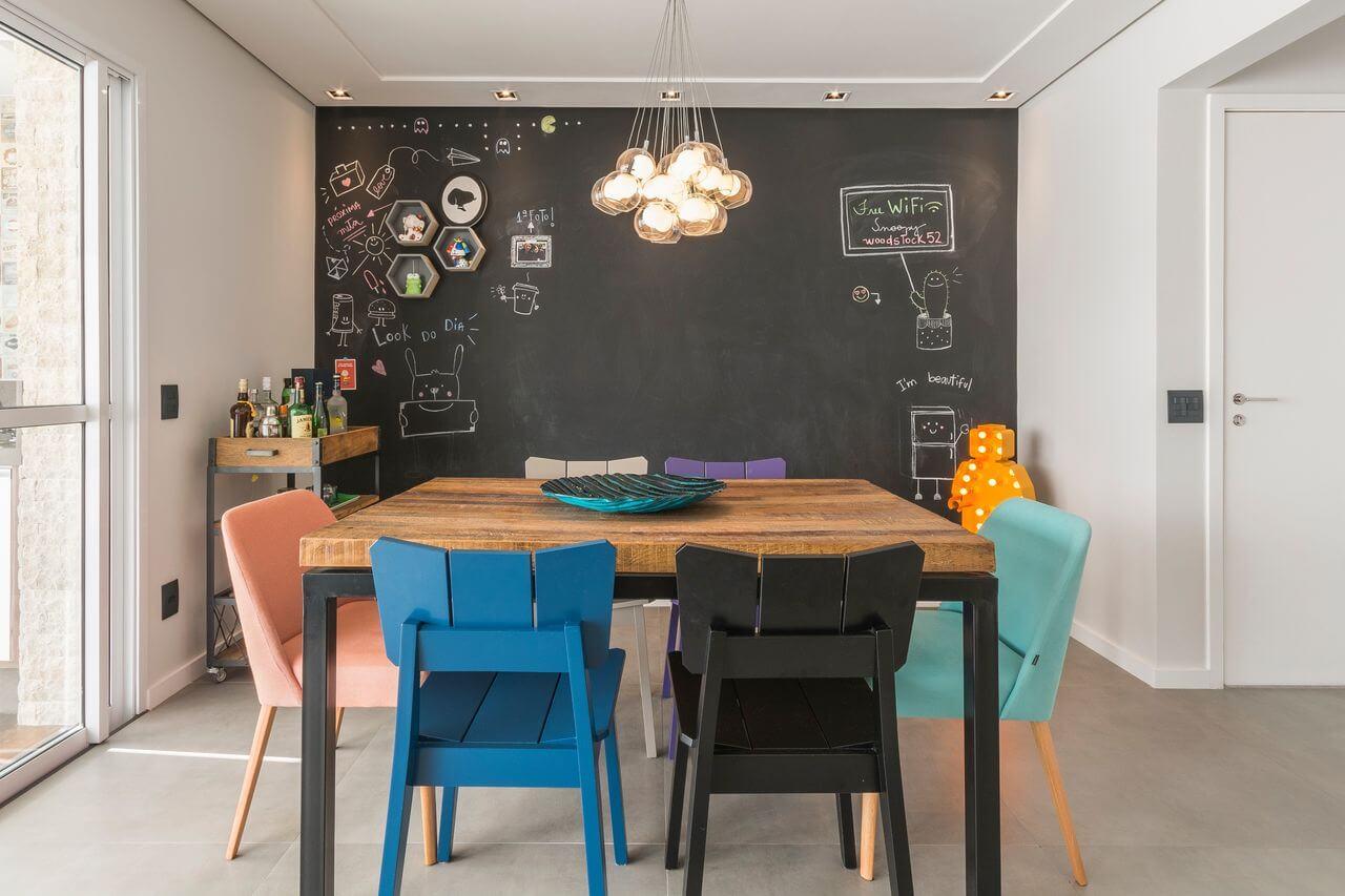 Sala de jantar pequena com cadeiras coloridas e parede de lousa Projeto de Idealizzare Arquitetura